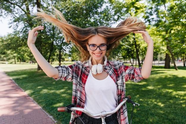 Langharige europese vrouw die in vrijetijdskleding oprecht geluk uitdrukt. zalig wit meisje poseren op de fiets in de lente.