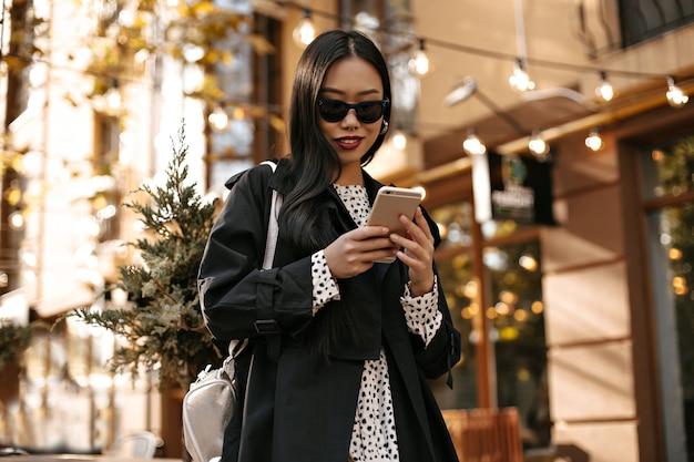 Langharige gebruinde vrouw in zwarte trenchcoat en witte polka dot jurk glimlacht en berichten aan de telefoon