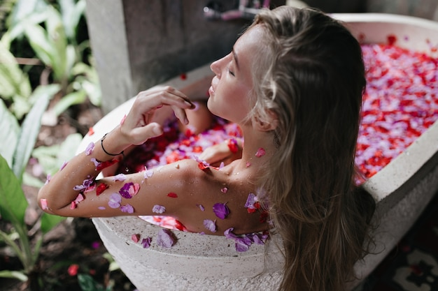 Langharige gelooide vrouw die van kuuroord in weekend geniet. blond vrouwelijk model liggend in bad met bloemblaadjes en koelen met gesloten ogen.
