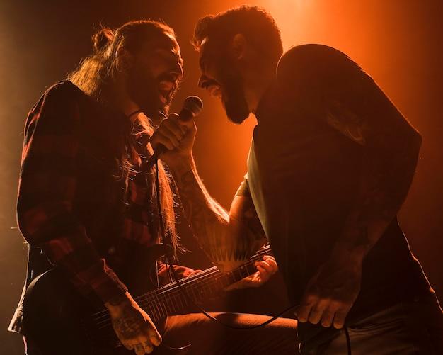Langharige gitaarman en vocalist duet zingen