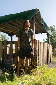 Langharige hippieman in t-shirt met militaire print en korte broek staat in de buurt van het tuinhuis en trekt gezichten.