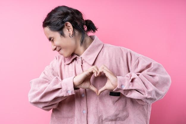 Langharige jonge aziatische man, gekleed in roze shirt, glimlachend op roze achtergrond