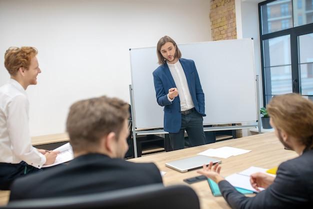Langharige jonge man in pak praten in de buurt van stand en lachende collega's tegenover zitten