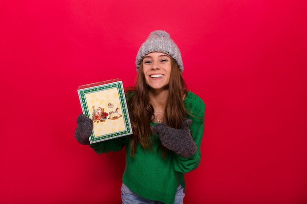 Langharige jonge vrouw in groene trui en grijze gebreide pet met kerstcadeau op rood