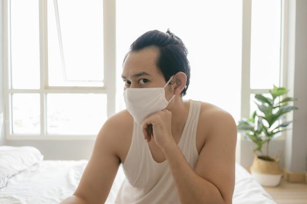 Langharige man met hygiënisch masker verveelt zich in quarantaine