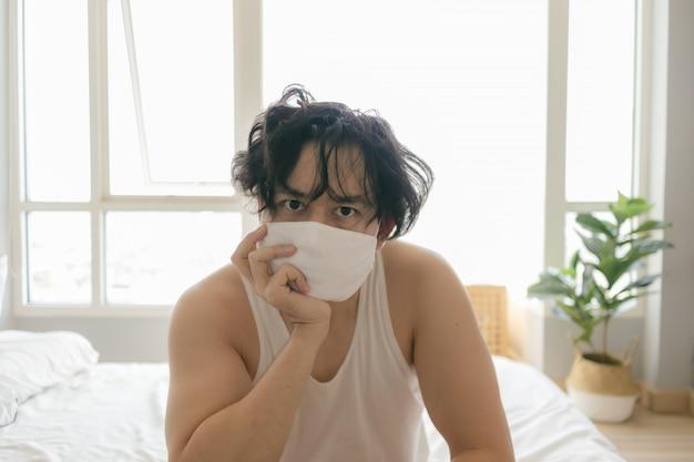 Langharige man met hygiënisch masker verveelt zich van quarantaine.