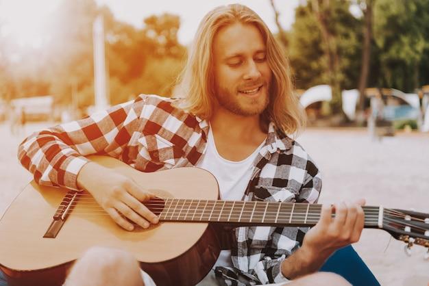 Langharige manmuzikant gitaarspelen op het strand.