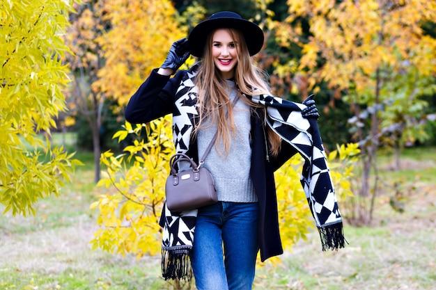 Langharige meisje draagt jeans spelen met haar sjaal in herfst park. aantrekkelijke jonge vrouw in stijlvolle zwarte hoed tijd doorbrengen in bos en lachen.