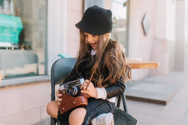 Langharige opgewonden meisje, zittend op de stoel in terras en spelen met retro camera. openluchtportret van geïnteresseerd krullend kind dat op moederfotograaf wacht die haar spullen houdt.