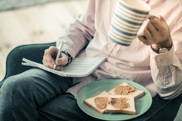 Langharige schepper. kerel in licht shirt die een nieuwe compositie maakt en thee drinkt tijdens de lunchpauze