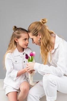 Langharige volwassen vrouw die diep in de ogen van haar kleine vriend kijkt terwijl ze samen lentebloemen draagt