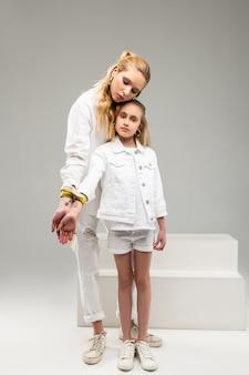 Langharige vreedzame vrouw die contact heeft met een klein meisje terwijl ze slot en sleutel om de polsen presenteert