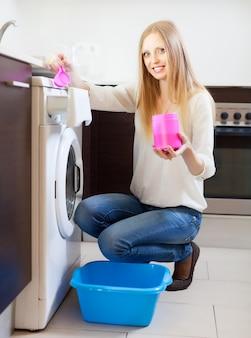 Langharige vrouw die wasserij met detergens doet