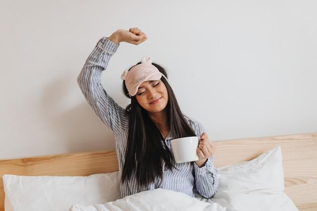Langharige vrouw in blauwe pyjama strekt zich zoet uit na het slapen
