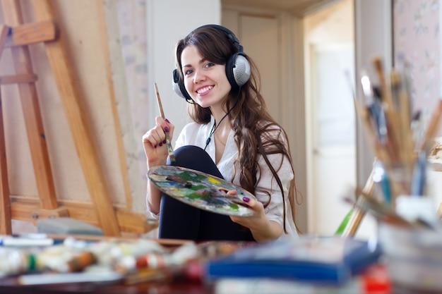 Langharige vrouw in hoofdtelefoon schildert met olie kleuren