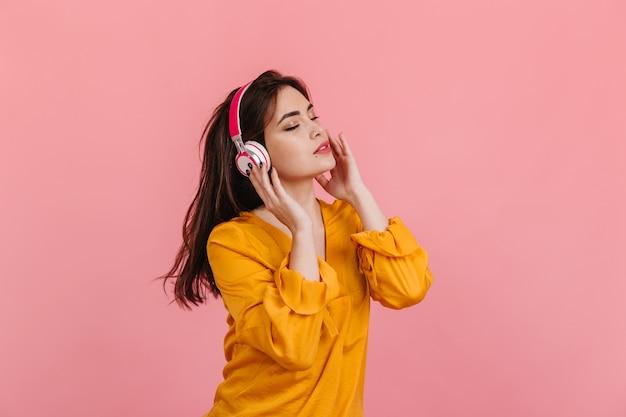 Langharige vrouw in lichte blouse en witte en roze koptelefoon luisteren naar muziek op geïsoleerde muur.