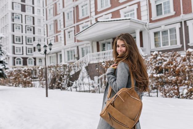 Langharige vrouw met bruine rugzak die langs prachtig gebouw in winterdag loopt. outdoor portret van prachtige brunette vrouw kijkt over de schouder tijdens het verkennen van de stad in besneeuwde ochtend.