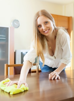 Langharige vrouw veegt het stof van tafel af