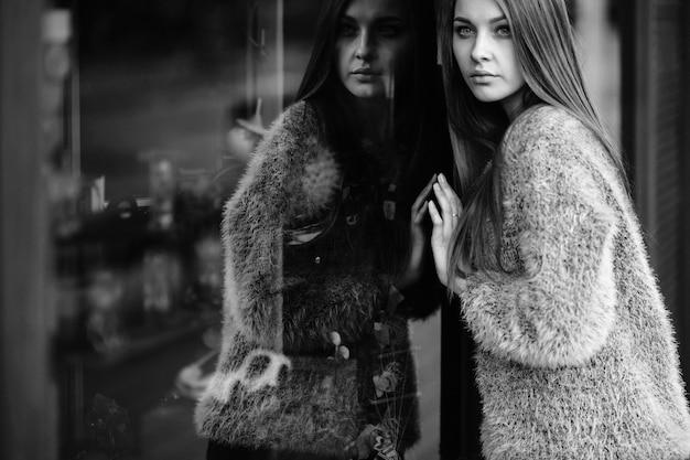 Langharige vrouw weerspiegeld in venster.