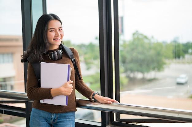 Langharige vrouwelijke student die een boek houdt en bij de universiteit stelt