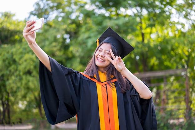Langharige vrouwelijke studenten die zwarte ruches dragen die vreugde uitdrukken bij het afstuderen aan de universiteit.