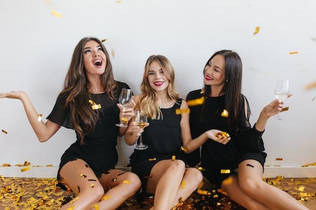 Langharige vrouwen die confetti met verbaasde gezichtsuitdrukking bekijken tijdens feestje