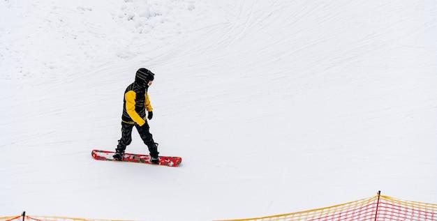 Langlaufen in prachtig winterlandschap. mannelijke snowboarder loopt op de heuvel. toeren in de bergen. bewolkt weer. sportconcept