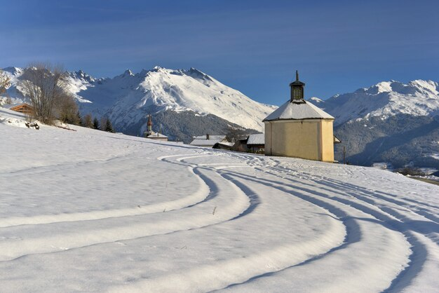 Langlaufpistondruk naar een klein kapelletje in een prachtig besneeuwd berglandschap