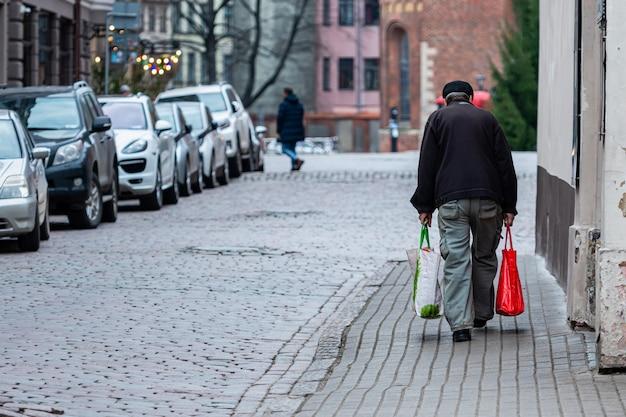Langs de geplaveide straten van de oude stad gaat een oude man met tassen. achteraanzicht