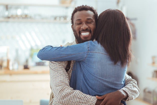 Langverwachte ontmoeting. charmante jongeman die zijn beste vriend knuffelt nadat hij haar in het koffiehuis heeft ontmoet na een lange periode zonder elkaar te hebben gezien