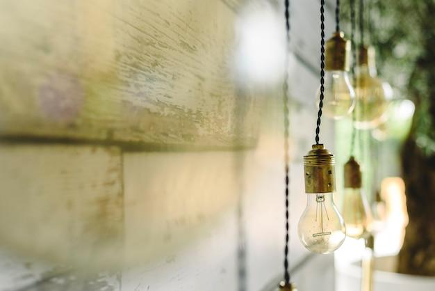 Langwerpige decoratiebollen die aan het houten plafond hangen.