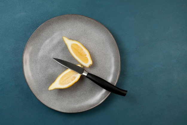 Langwerpige ongebruikelijke citroen, in de lengte gesneden, ligt op een grijze getextureerde plaat. in de buurt ligt mes. lelijk fruit.