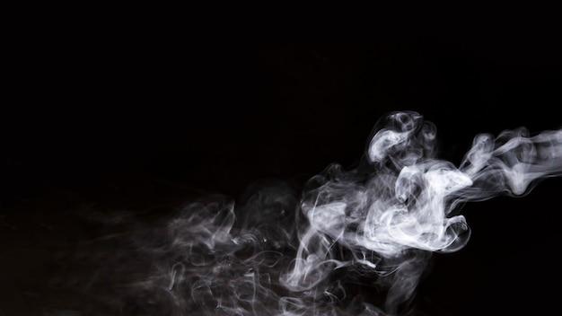 Langzaam verdwenen witte rook tegen zwarte achtergrond