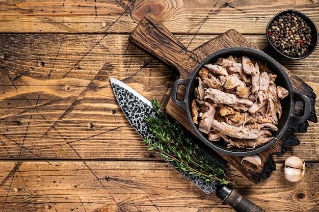 Langzaam versnipperd puilled varkensvlees in een pan met slagersmes. houten achtergrond. bovenaanzicht. ruimte kopiëren.