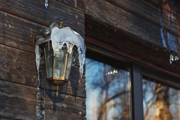Lantaarn aan de muur is bedekt met ijspegels
