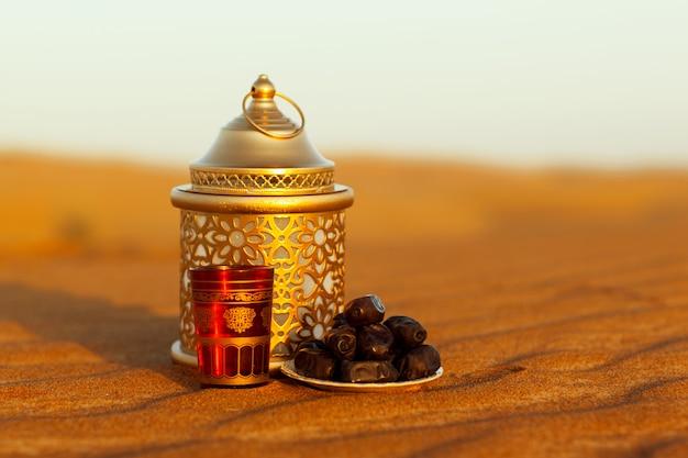 Lantaarn, beker en dadels liggen op het zand in de woestijn