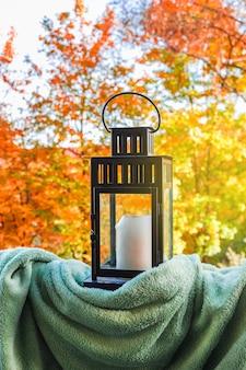 Lantaarn met een kaars en plaid op het terras natuur achtergrond van herfst kleurrijke garde