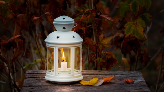 Lantaarn met een kaars op een achtergrond van de herfstbladeren in de donkere avond.