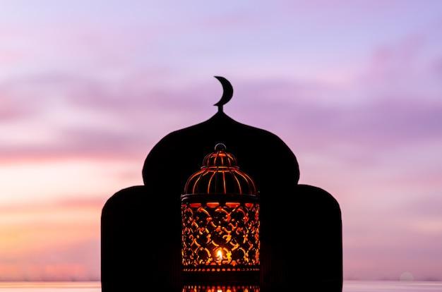 Lantaarn met wazige focus van moskeeachtergrond met maansymbool bovenaan en dageraadhemel