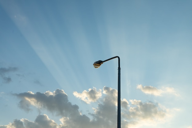 Lantaarnpaal in avondlucht met de stralen van de ondergaande zon.