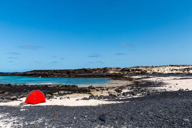 Lanzarote aan de voet van enorme vulkanische kliffen, vanaf het strand van caleton blanco. de voorgrond wordt gedomineerd door een gebogen windscherm van lavasteen ondergedompeld in azuurblauw zeewater.