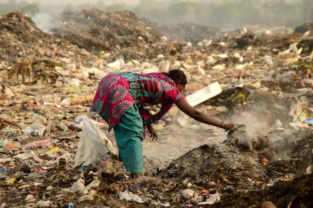Lappenplukkers zoeken naar recyclebaar materiaal in het vuilnisland en naar luchtvervuiling in india