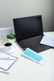 Laptop blanco mock-up. alcoholdesinfecterend middel op office werkplek op witte tafel. beschermend medisch blauw masker, desinfecterende spray. nieuwe normale normen voor thuishygiëne op kantoor tijdens coronavirus covid 19
