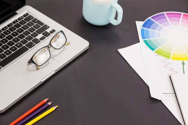 Laptop, bril, kleurpotloden, koffiekopje en kleurenschema