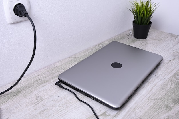 Laptop, computer laadt op vanaf een stopcontact van 220 volt op een bureau bij de muur. energie, accumulatie.