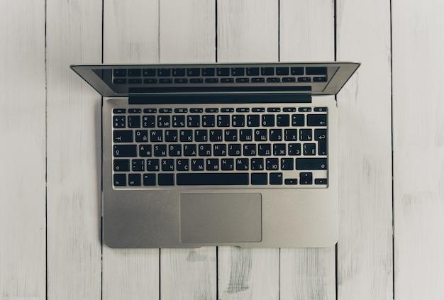 Laptop computer op een houten bureau, de ruimte van het hoogste meningsexemplaar