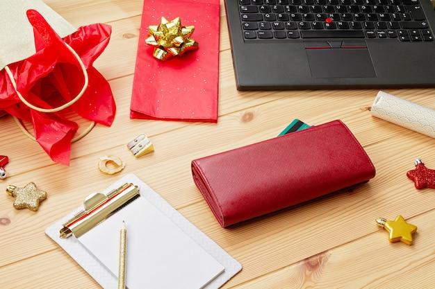 Laptop, creditcards, portemonnee en kerstversiering. online kerstinkopen, geschenken kopen