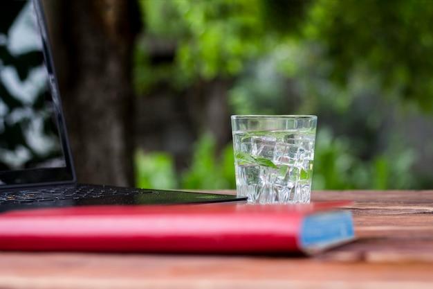 Laptop, dagboek en een glas met een verfrissend koud drankje met ijsblokjes en muntblaadjes op een houten tafel. het concept van werk in de natuur, freelancen, werk op vakantie