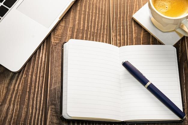 Laptop dagboek en koffiekopje op het bureau of op de houten tafel bovenaanzicht met kopie sleuf voor ontwerp