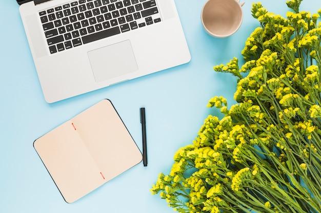 Laptop; dagboek; pen; lege keramische cup en bloemboeket tegen blauwe achtergrond